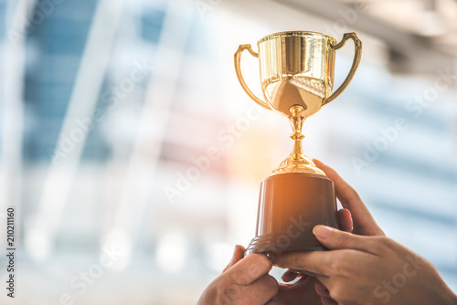 Leinwanddruck Bild Champion golden trophy for winner background. Success and achievement concept. Sport and cup award theme.