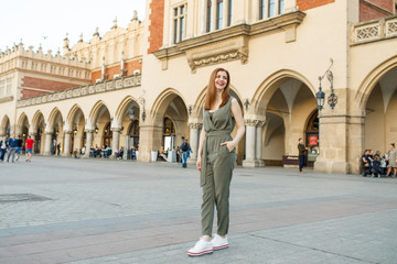 young beautiful girl in a black jacket is standing on the central square in Krakow in Poland