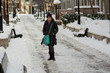 Woman standing on a snow covered street