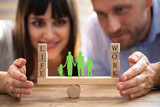 Couple Protecting Balance Between Work And Life On Seesaw - 210272144