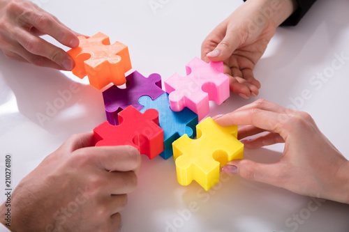 Foto Murales Group Of Businesspeople Solving Jigsaw Puzzle
