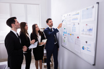 Businesspeople Analyzing Graphs On White Board © Andrey Popov