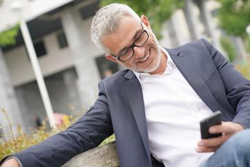 Businessman sitting on public bench using smartphone