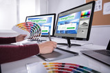 Designer Working On Multiple Computer Screens - 210283501