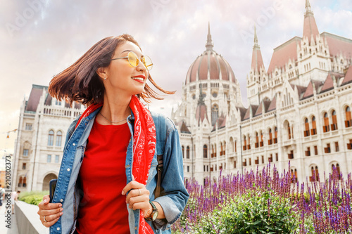 Fototapeta Happy asian casual woman student enjoying great view of the Parliament building in Budapest city, travel in Europe concept