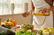Female food blogger wearing apron pouring olive oil into vegetable salad while standing at modern kitchen, close-up shot