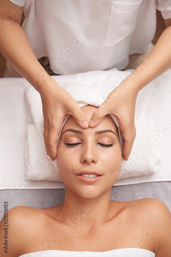 Overview of young woman enjoying facial spa massage in Asian beauty salon