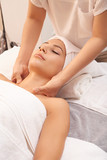 Cosmetician making neck massage while her client relaxing on soft towels