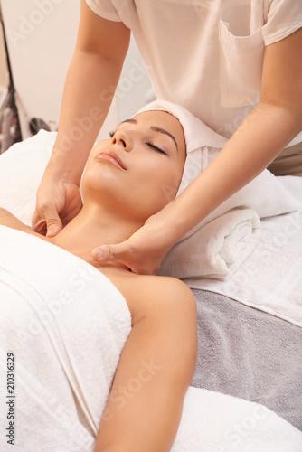Kosmetyczka robi masaż karku, a jej klientka odpoczywa na miękkich ręcznikach