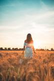 Bellissima ragazza con vestito bianco in mezzo a un infinito campo di grano al tramonto. - 210333197