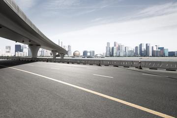 asphalt road with city skyline