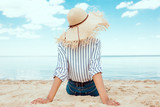 rear view of woman in straw hat relaxing on sandy beach - 210340742