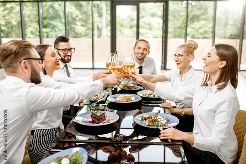 Group of business people dressed in white shirts clinking with wine glasses during a business lunch with delicious meals at the modern restaurant