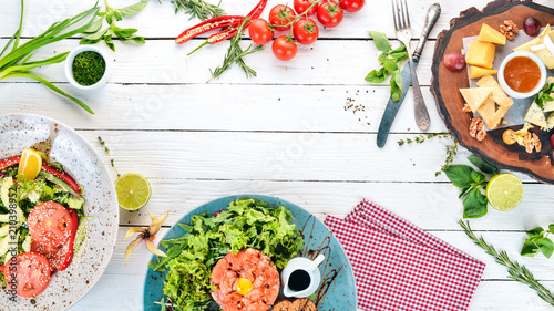 A set of food. Tartar, cheese, salad and vegetables. On a wooden background. Top view. Copy space. - 210398952