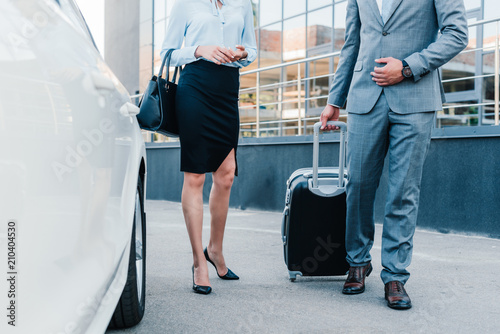 partial view of business people with luggage walking to car on parking - 210404530