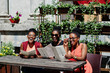 Three stylish african american womans posed at sunny summer day outdoor, sitting on table of restaurant with menu at hands.