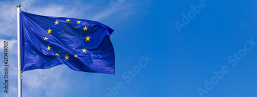Leinwandbild Motiv Flag of the European Union waving in the wind on flagpole against the sky with clouds on sunny day, banner, close-up