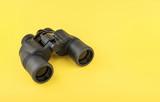 Binoculars on yellow background