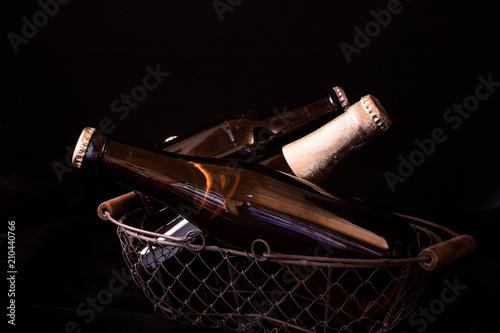 Fototapeta beer bottles on a black background chiaroscuro in an old metal mesh basket