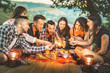 Leinwanddruck Bild - Happy friends having fun with fire sparkles - Young people millennials camping at picnic after sunset - Young people enjoying wine at summer barbecue party - Youth friendship concept on night mood