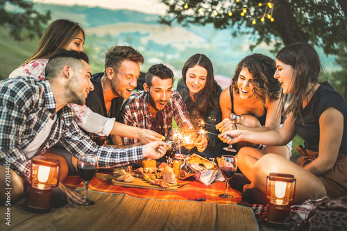 Leinwanddruck Bild Happy friends having fun with fire sparkles - Young people millennials camping at picnic after sunset - Young people enjoying wine at summer barbecue party - Youth friendship concept on night mood