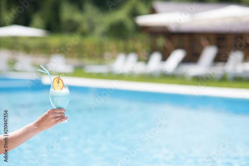 Trzymać pięknego koktajl na pływackiego basenu tle outdoors