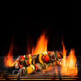 Delicious skewers on grill with Fire flames. - 210457310