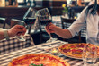 Verliebtes Paar stoßen auf Ihre Lieben an, halten Hand in einem Restaurant und essen Pizza und trinken Rotwein