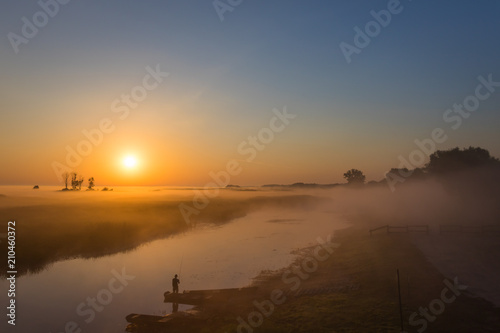 Plexiglas Zonsopgang Foggy landscape with a fisherman standing on the river shore at dawn under the rising sun