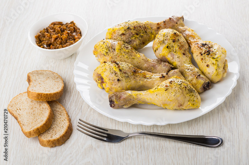 Fried chicken legs in plate, eggplant caviar, pieces of bread © Evgeny
