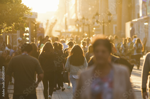 obraz PCV Silhouettes of people crowd walking down the street at summer evening, beautiful light at sunset