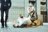 Starving man. Poor starving street man wearing tattered old clothes sitting outside the office center asking for help