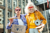 Bizarre hippies. Two bizarre elderly hippies feeling unbelievably amazing while performing in the street