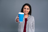 Delicious drink. Cheerful dark-haired woman showing a blue coffee cup to the camera and smiling brightly while posing isolated on a blue-grey background - 210483119