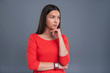 Weighing pros and cons. Charming young woman in a red dress thinking about something and resting her chin on her hand