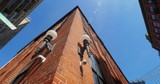 A low wide shot panning view looking up at red brick Brooklyn buildings.   - 210486954