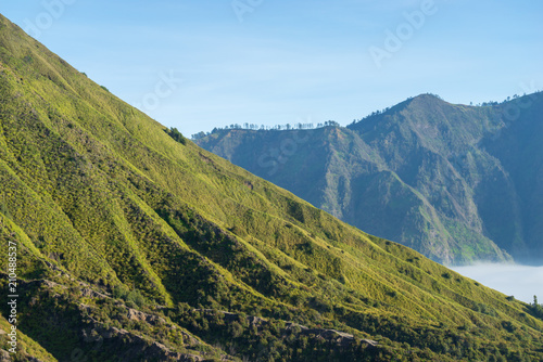 Mount Batok (2,470m), though lying adjacent to Mount Bromo. With a perfect triangular mountain top, rising from a sea of volcanic ash surrounding the Mount Bromo caldera. East Java of Indonesia.