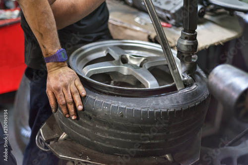 Professional mechanic using machine for tyre change. - 210496934