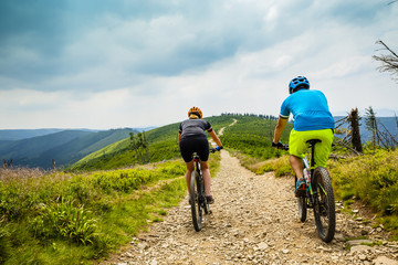 Cycling woman and man riding on bikes at sunset mountains forest landscape. Couple cycling MTB enduro flow trail track. Outdoor sport activity.