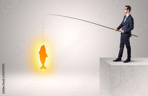 Młody biznesmen łowi złotą ryba z wierzchu budynku