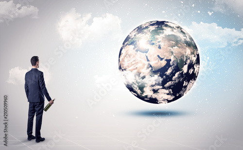 Fototapeta Businessman standing with his back with objects in his hand and looking at the globe, courtesy of NASA