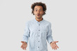 Are you kidding me? Waist up shot of attractive puzzled stupefied young African American male has dark stubble and Afro hairstyle, gestures in hesitation, dressed in white shirt, stands indoor.