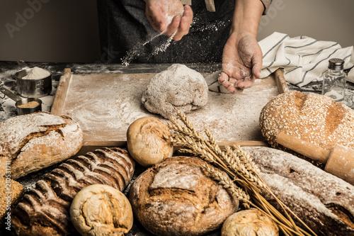 Fototapeta Bakery - baker's hands sprinkle raw dough with flour