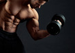 Frontview of strong bodybuilder with clear muscular relief lifting heavy dumbbell in gym. Sport lifestyle. Regular gym trainings. Fit sporty body. Lifestyle. Looking healthy and sexy. Working hard.