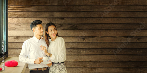 Fototapeta Asian Lover man and woman enjoy with a cup of coffee in coffee shop.