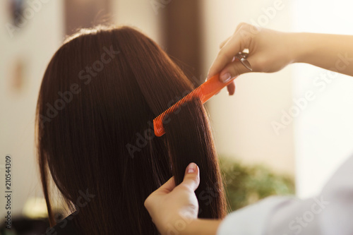 Stylist combing woman hair at salon - 210544309