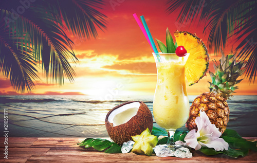 Pina colada fresh cocktail drink served on the beach at sunset