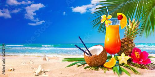 Leinwanddruck Bild Exotic cocktails served on the beach