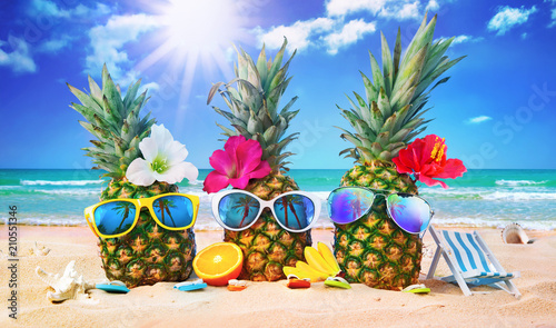 Leinwandbild Motiv Attractive pineapples in stylish sunglasses on the sand against turquoise sea