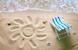 Deckchair on a beach with a sun drawn on the sand